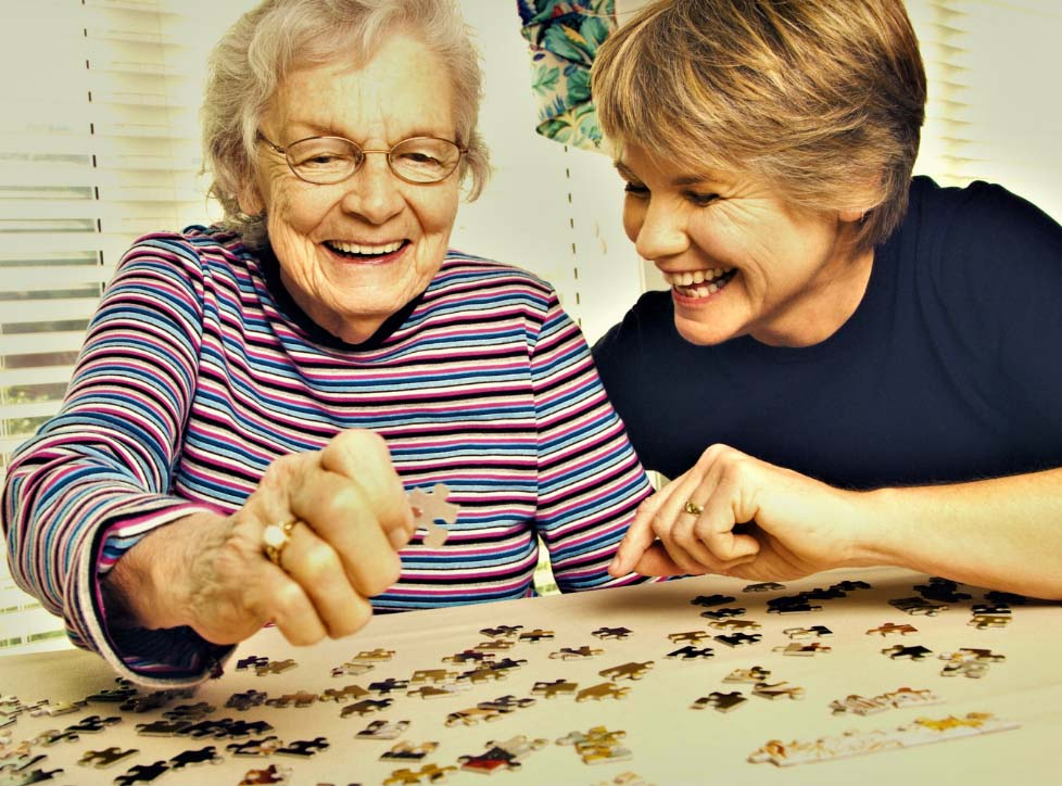 An elderly woman smiles while working with puzzle pieces