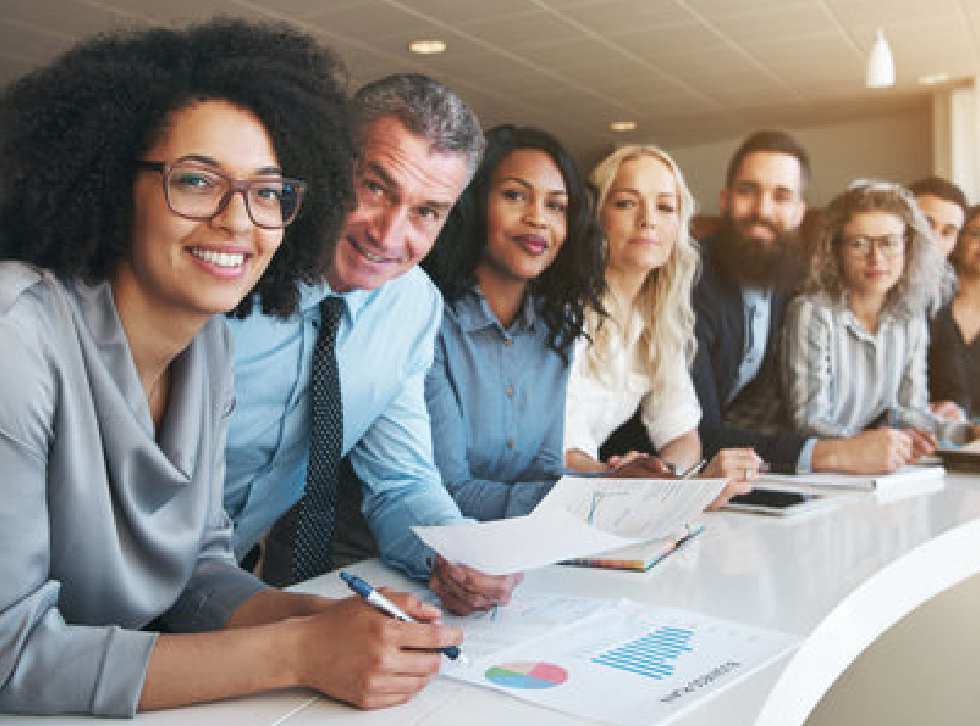 A group of smiling employees lean on a curved table.
