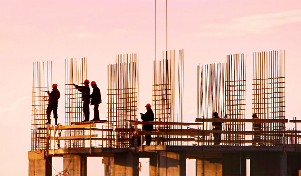 Iron workers at sunset on the top of a building under construction.