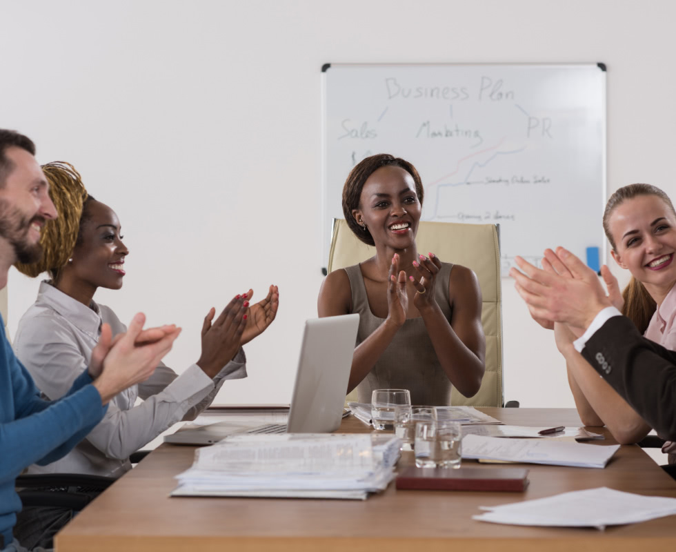 A group of employees work together at the conference room table.