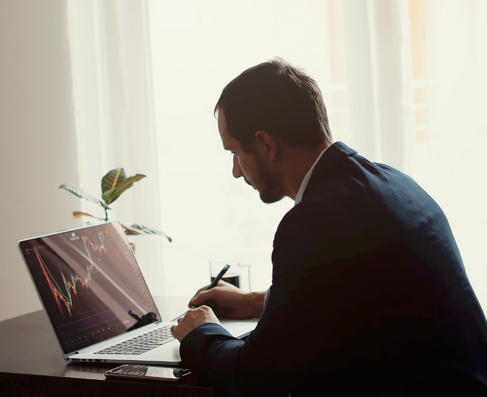 A man in a suit works at his desk on the computer