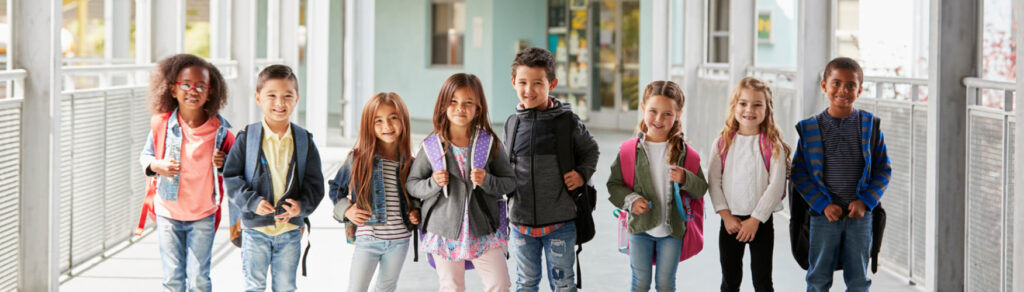 Children at a school pose with their backpacks on.