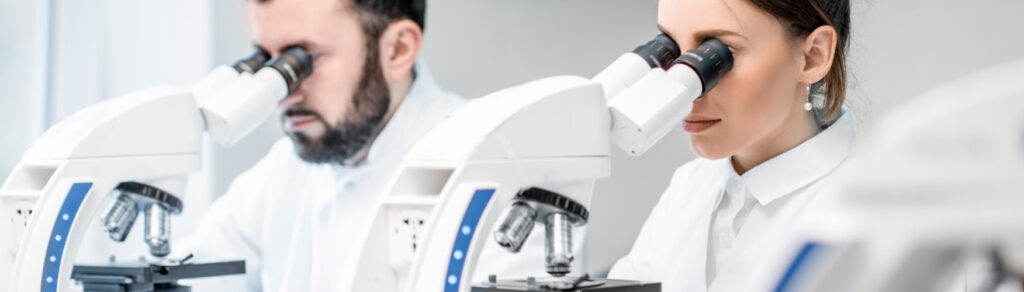 Two researchers look through microscopes in a white lab.